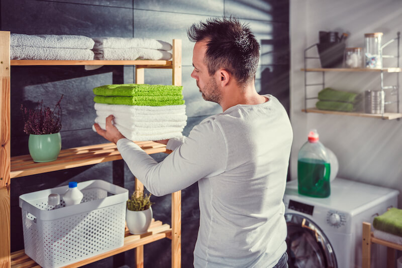 Men wearing white shirt arranging clean green towels at laundry room